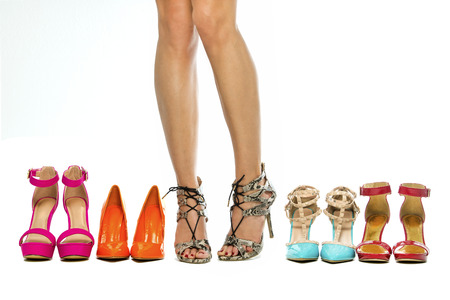 female sex: Beautiful female legs wearing high heels shoes and standing next to other various high heels.