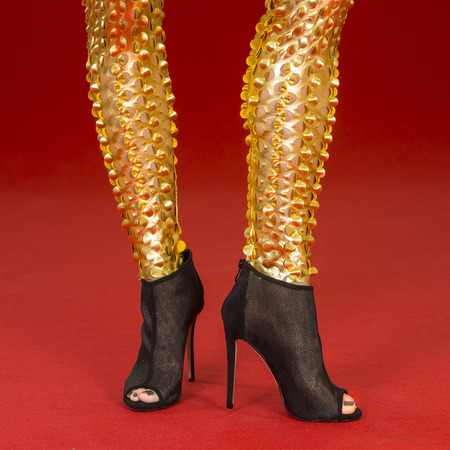 peep toe: sexy legs of a woman in fancy golden leggings and high heels on a red carpet Stock Photo