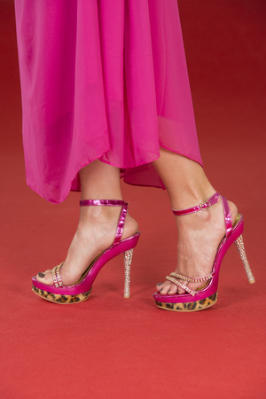 ankle strap: Sexy legs of a woman wearing a pink long dress and pink high heels shoes with animal print and rhinestone decoration on a red carpet.
