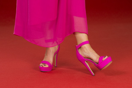 Sexy legs of a woman wearing a pink long dress and pink high heels shoes on a red carpet. Stock Photo