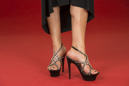 ankle strap: Sexy legs of a woman wearing a black dress and black high heels shoes with rhinestone decoration on a red carpet.