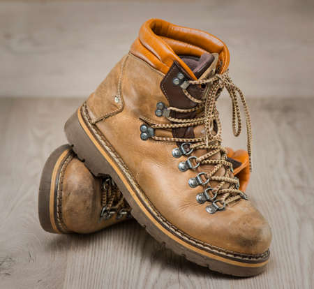 hiking boots: Mens working or hiking boots made of brown leather, vintage look, on wooden background.