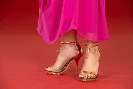 ankle strap: Sexy legs of a woman wearing golden high heels and a long pink dress on a red carpet. Stock Photo