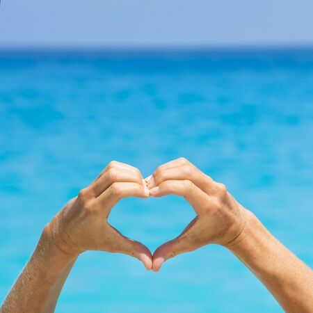 Female hands form a love heart against the blue ocean. Stock Photo