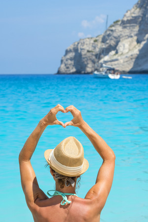 Female hands form a love heart against the blue ocean