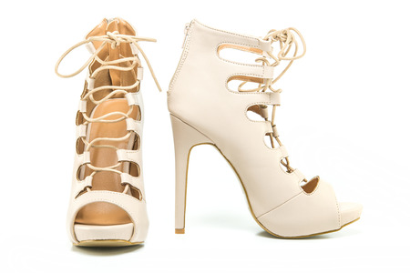 nude sex: fashionable stiletto high heels ankle boots in nude colour with laces, open toe and stiletto heel. Stock Photo