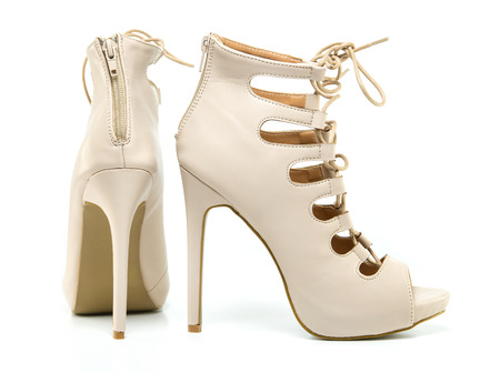 fashionable stiletto high heels ankle boots in nude colour with laces, open toe and stiletto heel. Stock Photo
