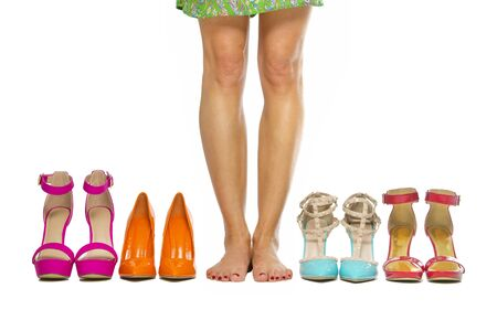 Woman is standing barefoot inbetween a group of fashionable high heels shoes.