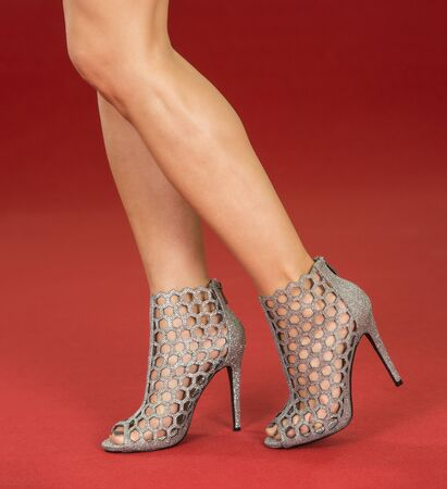 Sexy legs of a woman wearing high heels ankle boots in silver metallic design on a red carpet.