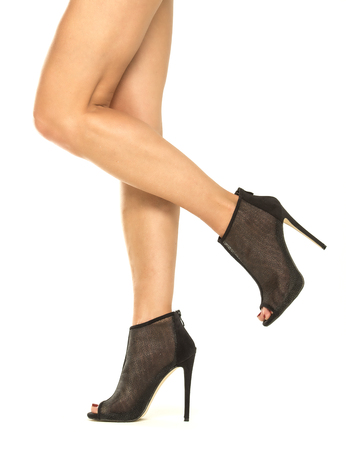 Beautiful female legs in shiny high heels ankle boots. The shoes are with small platform sole, open toe, ankle straps and made in a mesh fabric in black color. XXL image
