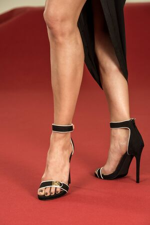 ankle strap: Sexy legs of a woman wearing a black dress and black high heels shoes on a red carpet. Stock Photo