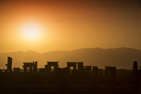 fars: Sunset behind the ruins of the ancient city of Persepolis in Iran. Persepolis was a capital of the Achaemenid Empire (550 - 330 BC). Persepolis is situated  about 60 km northeast of city of Shiraz in Fars Province in Iran. The earliest remains of Persepol Stock Photo