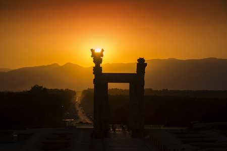 Sunset behind the ruins of the ancient city of Persepolis in Iran. Persepolis was a capital of the Achaemenid Empire (550 - 330 BC). Persepolis is situated  about 60 km northeast of city of Shiraz in Fars Province in Iran. The earliest remains of Persepol Stock Photo