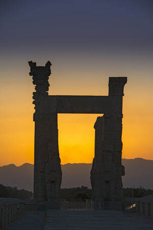 Sunset behind the ruins of the ancient city of Persepolis in Iran. Persepolis was a capital of the Achaemenid Empire 550 - 330 BC. Persepolis is situated  about 60 km northeast of city of Shiraz in Fars Province in Iran. The earliest remains of Persepolis