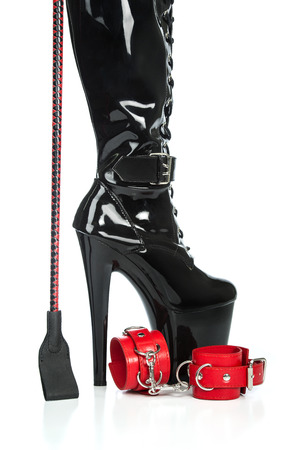 Fetish and bondage stuff for role playing and BDSM: extreme high heels boots, red leather cuffs, and a riding whip.