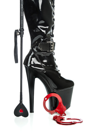 Fetish and bondage stuff for role playing and BDSM: extreme high heels boots, red metal hand cuffs, and a riding whip with a heart symbol.
