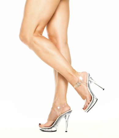 Female legs in transparent high heels shoes with platform sole Stock Photo