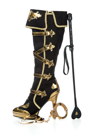 Fetish and bondage stuff for role playing and BDSM: high heels boots with plateau sole, leather whip and hand cuffs Stock Photo