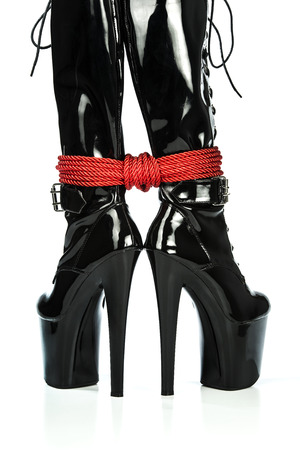Fetish and bondage stuff for role playing and BDSM: extreme high heels boots with red shibari rope.