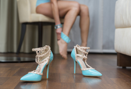 Blue stiletto high heels shoes, in the background woman with sexy long legs of a caucasian woman wearing stockings. Stock Photo