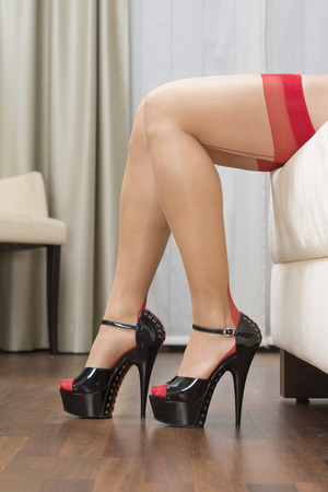 Sexy long legs of a caucasian woman wearing garter belt and stockings in nude and red. With high heels shoes with platform sole and ankle straps. Stock Photo