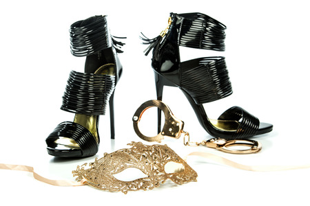 Fetish style high heels shoes with ankle straps in shiny black patent leather together with metal hand cuffs and a fetish mask in venetian style in golden color. Stock Photo