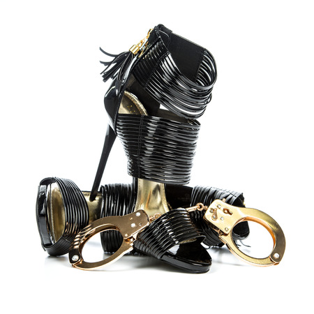 Fetish style high heels shoes with ankle straps in shiny black patent leather together with metal hand cuffs in gold.