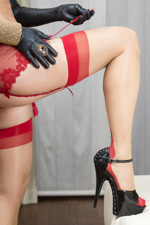 Sexy long legs of a caucasian woman who is attaching her stockings to a garter belt or suspender belt With high heels shoes with platform sole and ankle straps.