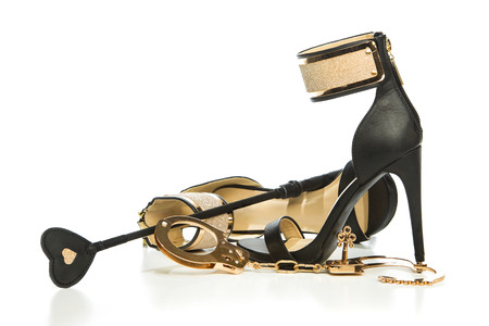 Fashionable High heels pumps in black with ankle strap in gold metal togehter with fetishbondage gear (golden handcuffs and leather whip).