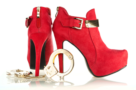 fashionable stiletto high heels ankle boots in red suede with golden buckle and golden metal hand cuffs; Stock Photo