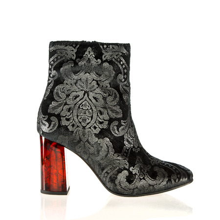 Fashionable high heels ankle boots in black and silver ornament design with a heel made in red shine plastic.Please note that this is no-name product from a chinese retail-market and NO branded designer product. Stock Photo