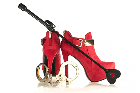 fashionable stiletto high heels ankle boots in red suede with golden buckle and golden metal hand cuffs and a black fetish whip; Please note that the shoes are a no-name product from a chinese retail-market and NO branded designer products. Stock Photo