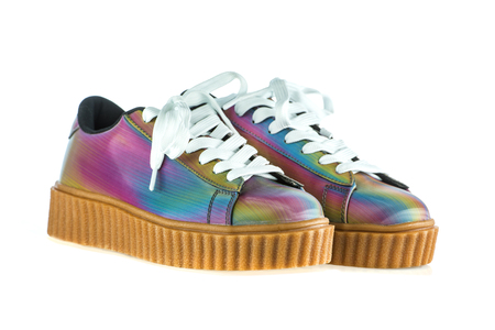 Fashionable platform sneakers with a holographic rainbow design. Stock Photo