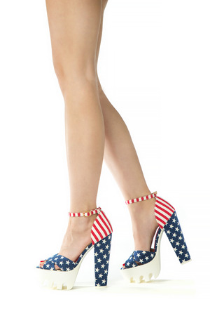 Studio shot of beautiful legs in hot pants in high heels with stars and stripes on white background. Stock Photo