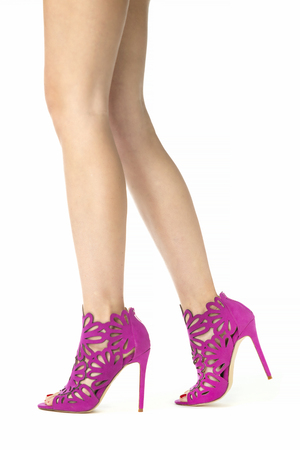 Long female legs in high heels ankle boots in pinklilac suede with cut-out ornate design