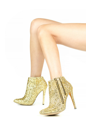Long female legs in high heels ankle boots in shiny gold with rhinestones and sequins.