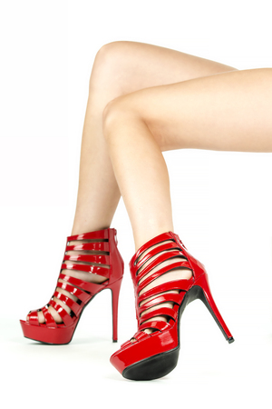 Long female legs in high heels ankle boots in shiny red patent leather.