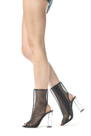 Long female legs in high heels ankle boots in transparent black mesh and clear plastic heels. Stock Photo