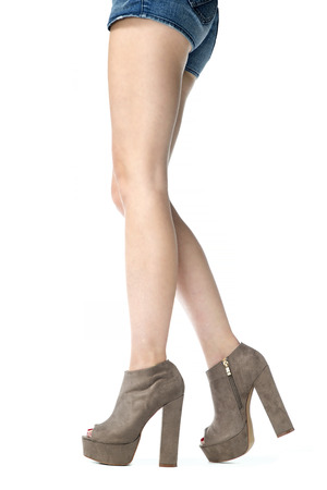 Long female legs in high heels ankle boots in taupe suede.