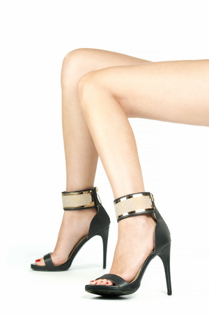Long female legs in high heels with a goldenmetalic ankle strap