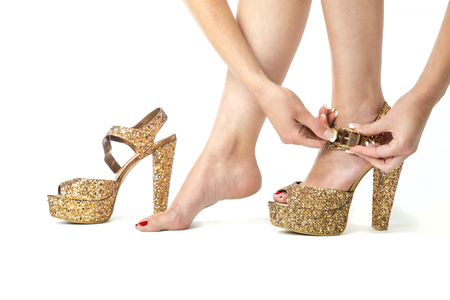 woman is closing ankle strap of sparkling golden high heels shoes.