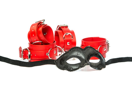 Stuff for sexual role playing: fetish mask in venetian style togehter with red hand cuffs. Stock Photo