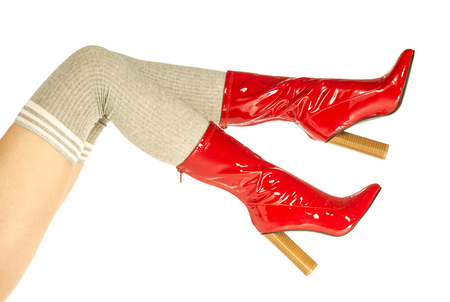 Beautiful female legs in high heels boots made out of red latex and kneesocks (thigh highs, over knee socks) in grey colour.