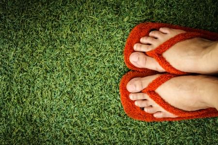 Feet in sneakers in green grass Stock Photo