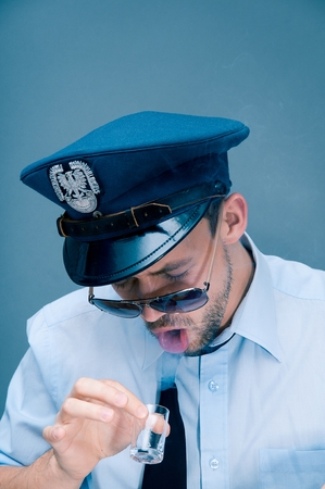 Policeman addicted to alcohol Stock Photo