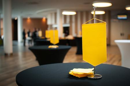 Tafel op het eerste plan met gele vlag in de vergaderzaal Stockfoto