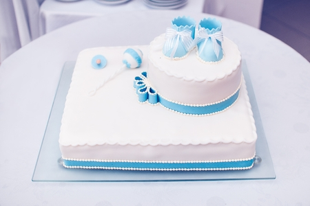 Blue cake with baby shoes in the top Zdjęcie Seryjne