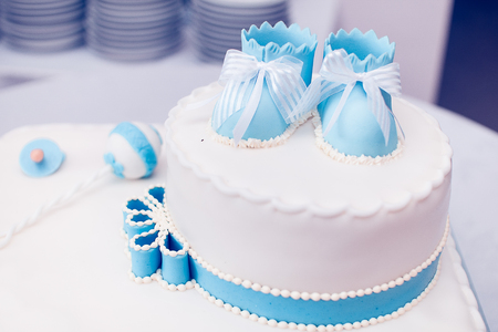 Blue cake with baby shoes in the top Stock Photo