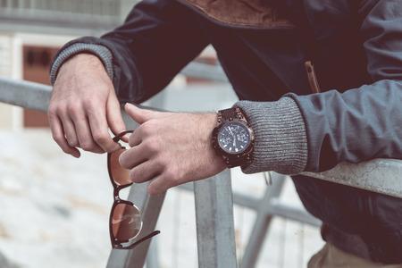 Relógio masculino de luxo e óculos escuros na mão do homem