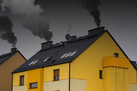 Modern non ecologic building with Chimney on the roof with smoke coming out, polluting the area Stock Photo